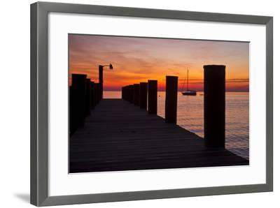 Sunrise on the Water with an Empty Dock and a Sailboat in the Distance of Tilghman Island, Maryland-Karine Aigner-Framed Photographic Print