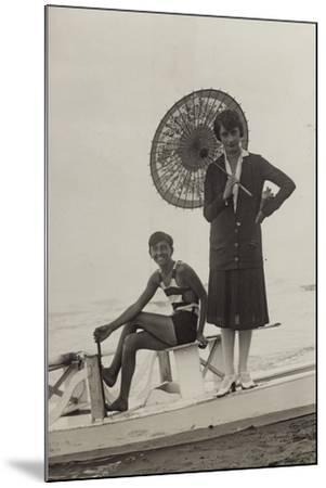 Young Woman with Umbrella and Boy on Pedal Boats on the Beach of Forte Dei Marmi--Mounted Photographic Print