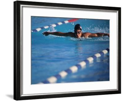 Female Swimmer Competing in a Butterfly Race--Framed Photographic Print