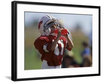 8 Year Old Boy Taking a Drink During a Football Game--Framed Photographic Print