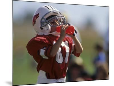 8 Year Old Boy Taking a Drink During a Football Game--Mounted Photographic Print