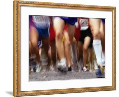 Blurred Action of Runner's Legs Competing in a Race--Framed Photographic Print