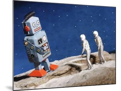 Astronaut Figurines Standing Beside Gray Toy Rocket--Mounted Photographic Print
