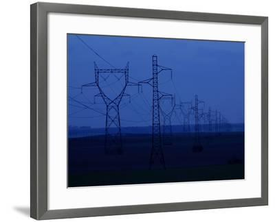Tall Towers Supporting Power Lines in a Dark Blue Sky--Framed Photographic Print