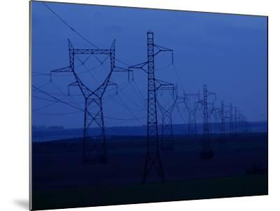 Tall Towers Supporting Power Lines in a Dark Blue Sky--Mounted Photographic Print