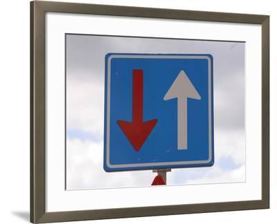 An Overcast Sky with a Blue Sign and a Red and a White Arrow--Framed Photographic Print