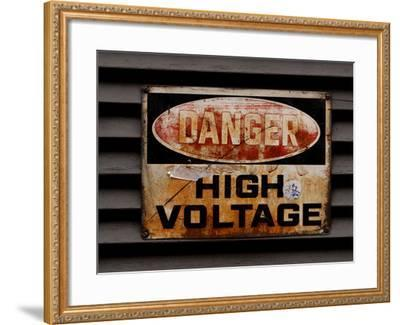 Close-up of a Faded Red and Black and White High Voltage Sign--Framed Photographic Print