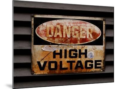 Close-up of a Faded Red and Black and White High Voltage Sign--Mounted Photographic Print