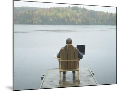 Man Sitting on a Dock Working on Laptop--Mounted Photographic Print