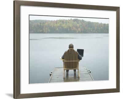 Man Sitting on a Dock Working on Laptop--Framed Photographic Print
