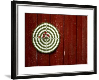 Old Dart Board Game Hanging on a Weathered Red Wall--Framed Photographic Print