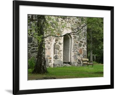 Wooden Bench in Peaceful Garden in Front of Stone Building--Framed Photographic Print