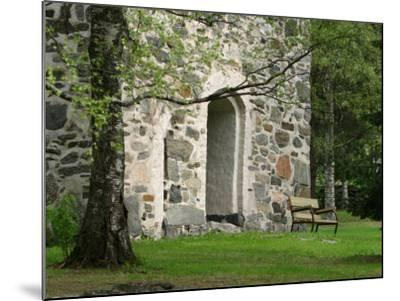 Wooden Bench in Peaceful Garden in Front of Stone Building--Mounted Photographic Print