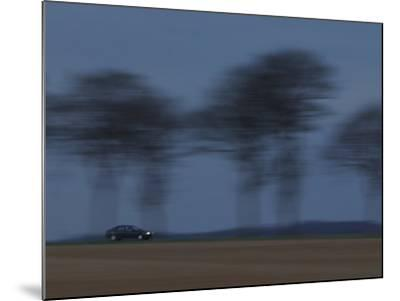 Motion Blur of Speeding Car on Tree-Lined Road in France--Mounted Photographic Print