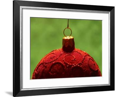 Close-Up of Red Christmas Decoration with Glitter Pattern Against Green Background--Framed Photographic Print