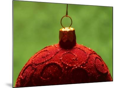 Close-Up of Red Christmas Decoration with Glitter Pattern Against Green Background--Mounted Photographic Print