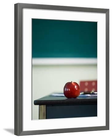 Bright Red Apple on Desk of Teacher in Classroom--Framed Photographic Print