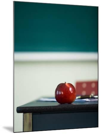 Bright Red Apple on Desk of Teacher in Classroom--Mounted Photographic Print