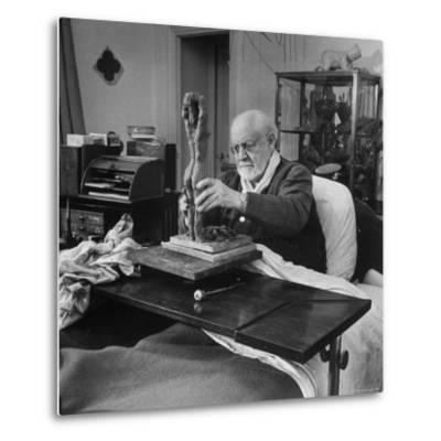 Henri Matisse Sculpting Nude Female Figure While Sitting in Bed in His Apartment-Dmitri Kessel-Metal Print