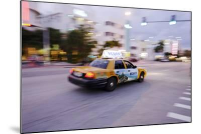 Taxi at Full Speed Early in the Evening on Collins Avenue, Miami South Beach, Florida-Axel Schmies-Mounted Photographic Print