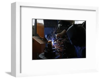 Man Welding Workpiece, Workshop, Flying Sparks- Fact-Framed Photographic Print