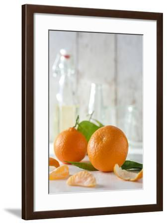Clementines with Foliage, Pieces of Clementines and Peel in Front of Bright Background-Jana Ihle-Framed Photographic Print