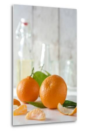 Clementines with Foliage, Pieces of Clementines and Peel in Front of Bright Background-Jana Ihle-Metal Print