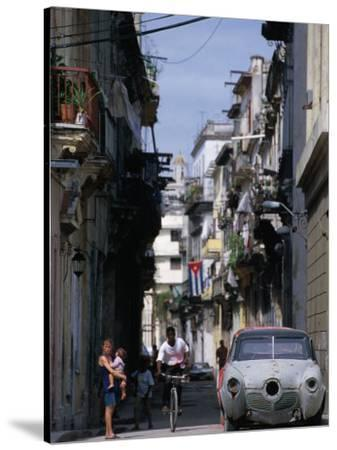 Woman with Baby, Man on Bicycle and Old Car in a Narrow Street Lined with Houses, Havana, Cuba-Rick Gerharter-Stretched Canvas Print