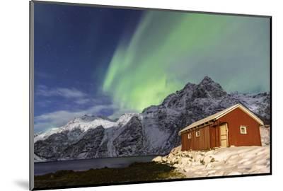Northern Lights (Aurora Borealis) Illuminate Snowy Peaks and Wooden Cabin on a Starry Night-Roberto Moiola-Mounted Photographic Print