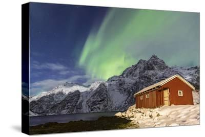 Northern Lights (Aurora Borealis) Illuminate Snowy Peaks and Wooden Cabin on a Starry Night-Roberto Moiola-Stretched Canvas Print