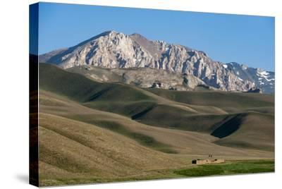 A Distant House in the Grasslands with Views of Mountains in the Distance, Bamiyan Province-Alex Treadway-Stretched Canvas Print