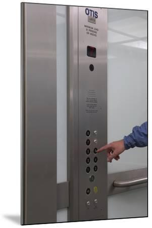 Man Pressing Lift Buttons, UK Office Interior-Richard Bryant-Mounted Photo