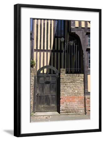 Timber Framed Building with Gate and Brick Wall in Tudor-Style House-Natalie Tepper-Framed Photo