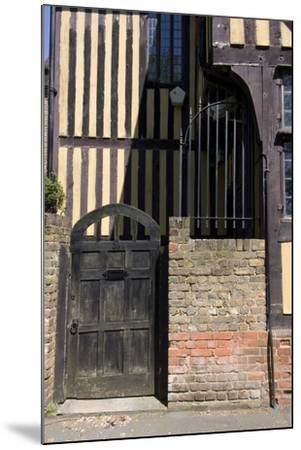 Timber Framed Building with Gate and Brick Wall in Tudor-Style House-Natalie Tepper-Mounted Photo