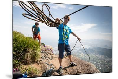 Young Man Standing on Top of the Mountain Holding Rope for Slacklining-Keith Ladzinski-Mounted Photographic Print