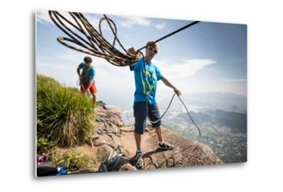 Young Man Standing on Top of the Mountain Holding Rope for Slacklining-Keith Ladzinski-Metal Print