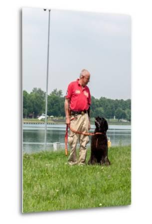 A Newfoundland Dog Trained for Rescue at Sea, with an Instructor at a Lake Near Milan-Lori Epstein-Metal Print
