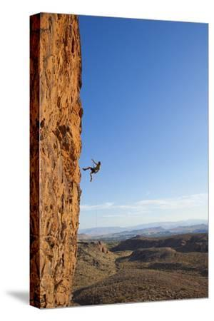 A Male Rock Climber Rappelling in Snow Canyon State Park-John Burcham-Stretched Canvas Print