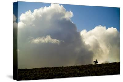 Silhouette of a Cowboy Riding across a Ridge with a Cumulonimbus Cloud in the Background-Jonathan Kingston-Stretched Canvas Print