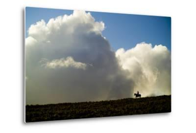 Silhouette of a Cowboy Riding across a Ridge with a Cumulonimbus Cloud in the Background-Jonathan Kingston-Metal Print