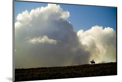 Silhouette of a Cowboy Riding across a Ridge with a Cumulonimbus Cloud in the Background-Jonathan Kingston-Mounted Photographic Print