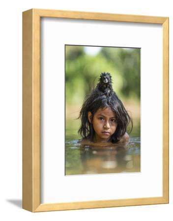 A Pet Saddleback Tamarin Hangs on Tight to a Matsigenka Girl as She Swims in the Yomibato River-Charlie Hamilton James-Framed Photographic Print