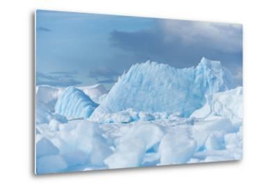 Blue Iceberg Floats Amidst Sea Ice in Fournier Bay, Antarctica-Jeff Mauritzen-Metal Print