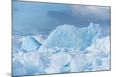 Blue Iceberg Floats Amidst Sea Ice in Fournier Bay, Antarctica-Jeff Mauritzen-Mounted Photographic Print
