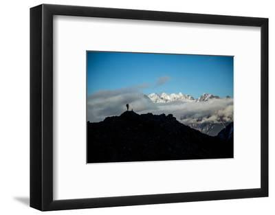 A Mountaineer Stands on a Mountaintop with Higher Peaks Visible in the Sunlight Beyond-Cory Richards-Framed Photographic Print