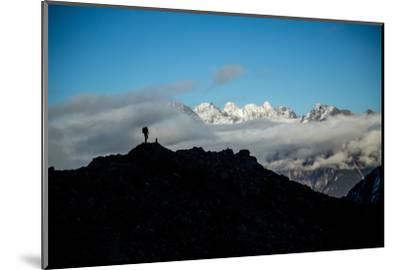A Mountaineer Stands on a Mountaintop with Higher Peaks Visible in the Sunlight Beyond-Cory Richards-Mounted Photographic Print
