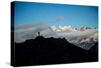 A Mountaineer Stands on a Mountaintop with Higher Peaks Visible in the Sunlight Beyond-Cory Richards-Stretched Canvas Print