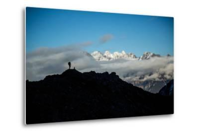 A Mountaineer Stands on a Mountaintop with Higher Peaks Visible in the Sunlight Beyond-Cory Richards-Metal Print
