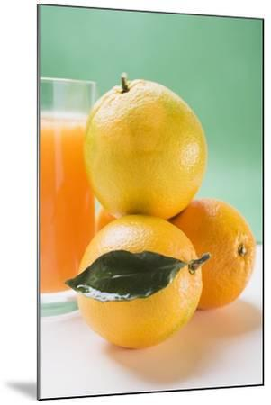 Glass of Orange Juice Beside Several Oranges-Foodcollection-Mounted Photographic Print
