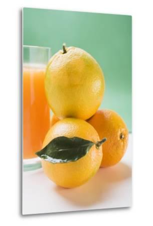 Glass of Orange Juice Beside Several Oranges-Foodcollection-Metal Print